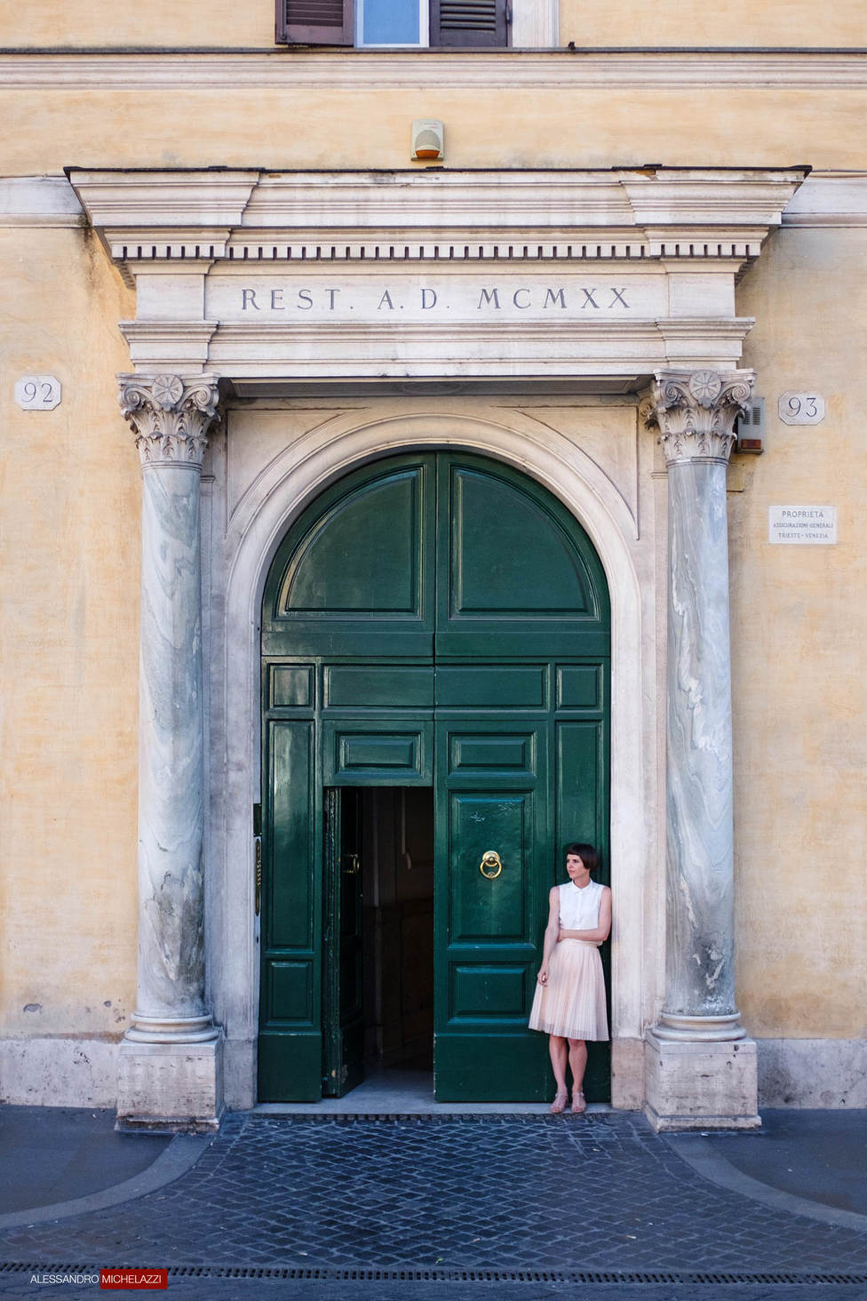 Lady waiting in front of a door in Rome
